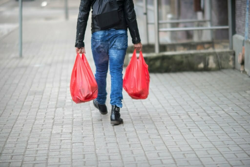 Man Carrying Plastic Bags While Walking On Sidewalk