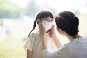 Mother putting on mask to girl